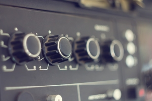 Piece of electrical audio equipment with knobs. Old retro amplifier with selective focus